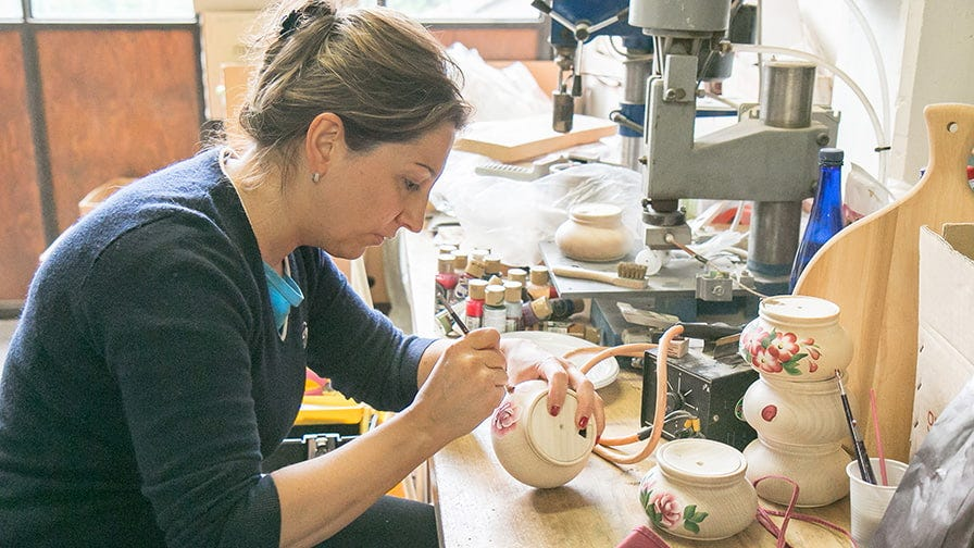 Noris paints the bowls by hand